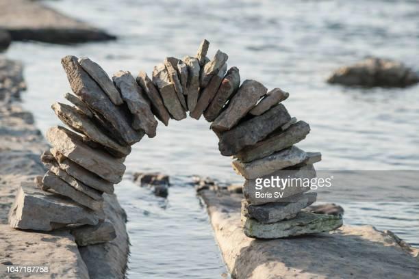 rock balancing. arch above water - kiesel stock-fotos und bilder