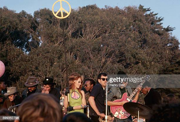 A rock band and a gogo dancer perform on stage at the Human BeIn Golden Gate Park San Francisco California USA