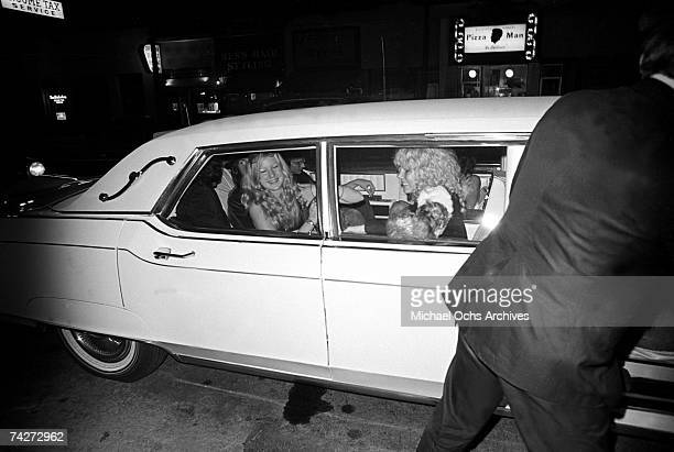 Rock band 'Led Zeppelin' ride in a white limousine adorned with various groupies outside of Rodney Bingenheimer's English Disco in June 1972 in Los...