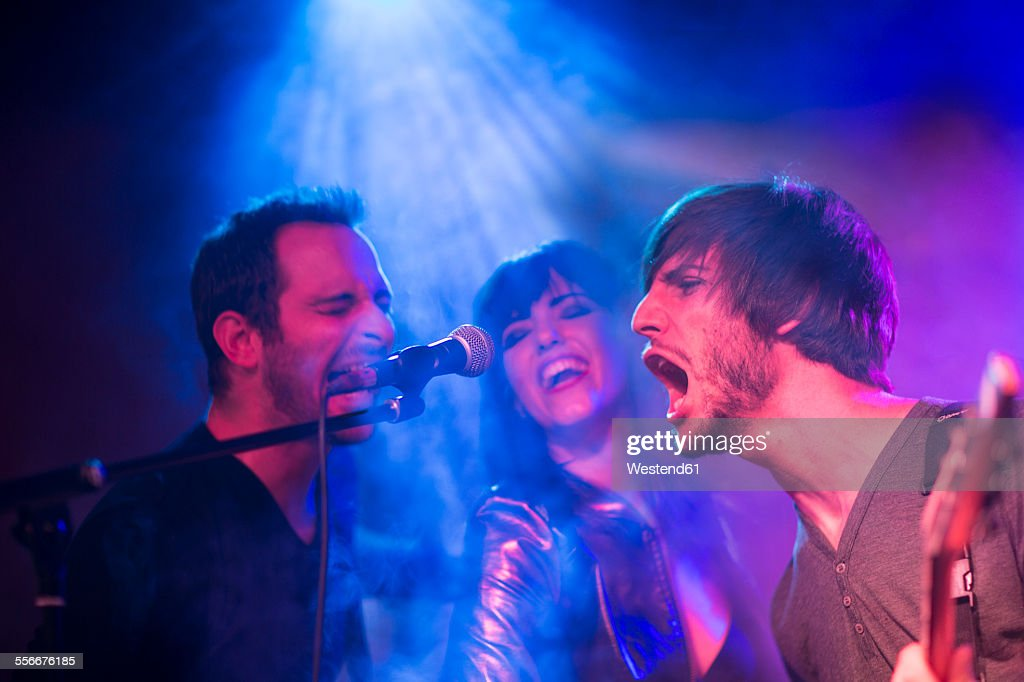 Rock band on stage screaming into microphone : Stock Photo