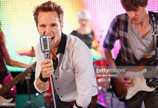 rock band performing on stage - singer stock pictures, royalty-free photos & images
