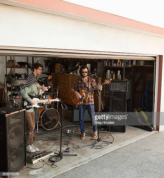 rock band rehearsing in garage - garage band stock photos and pictures