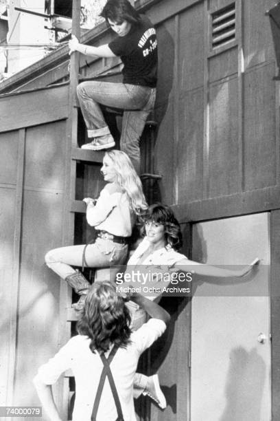 Rock band 'The Runaways' climbing a ladder in 1977