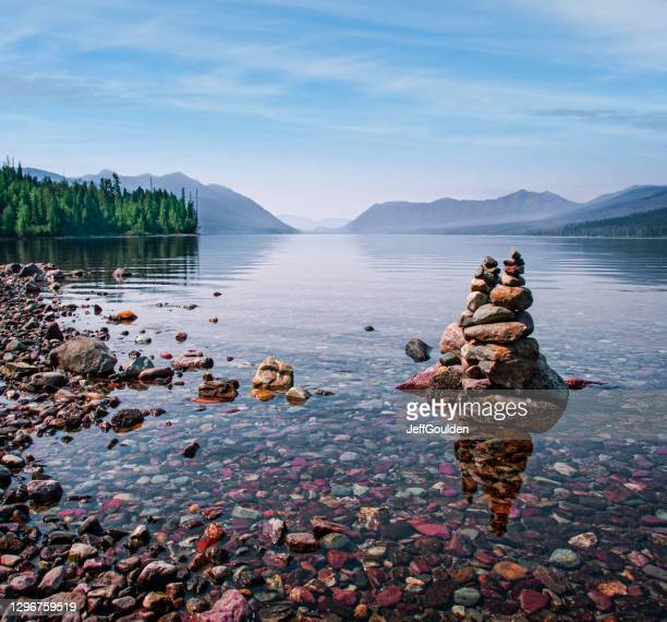 rock cairn at lake mcdonald - jeff goulden stock pictures, royalty-free photos & images