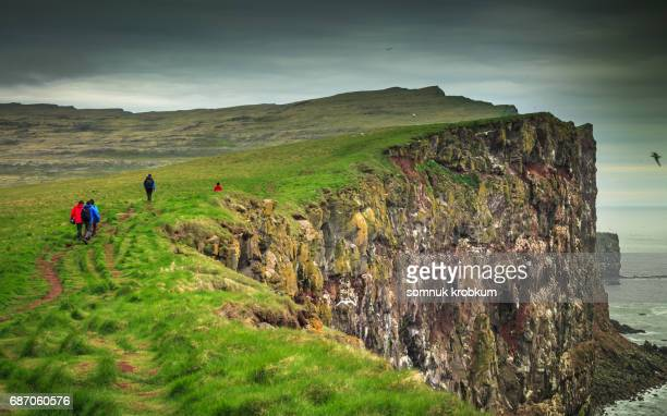 rock cliff with tourists in summer;iceland - westfjords iceland stock photos and pictures