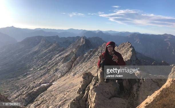 rock climber and mountaineer holding camalots climbing equipment while sitting on top of the matterhorn peak overlooking the crumbling granite mountain cliffs of the sawtooth ridge traverse in the high sierra near bridgeport california - pinnacle peak stock pictures, royalty-free photos & images
