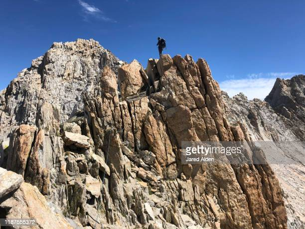 rock climber and mountaineer wearing a backpack stands on top of the crumbling granite cliffs of the doodad tooth on the sawtooth ridge traverse of the high sierra mountains with the matterhorn peak in the background near bridgeport california - pinnacle peak stock-fotos und bilder