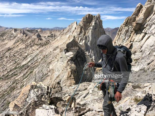 rock climber and mountaineer with climbing equipment, backpack and helmet, walking on loose granite rocks high up on the sawtooth ridge traverse near the doodad gap under matterhorn peak nearby bridgeport california - pinnacle peak stock pictures, royalty-free photos & images