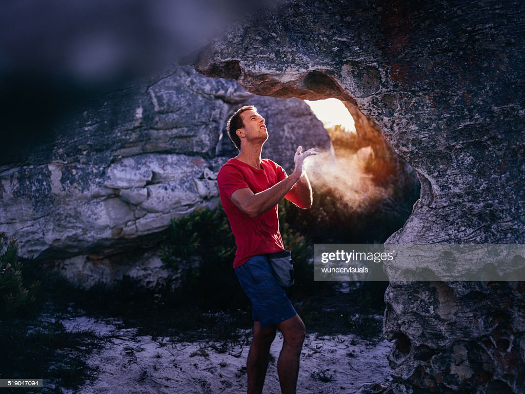 Rock climber applying chalk to hands in preparation for climbing : Stock Photo