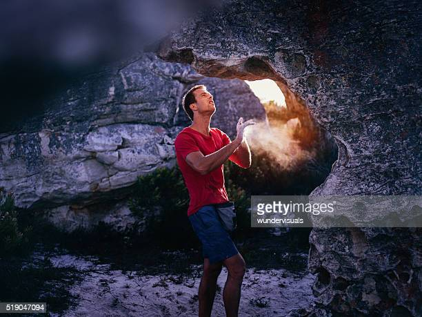 Rock climber applying chalk to hands in preparation for climbing