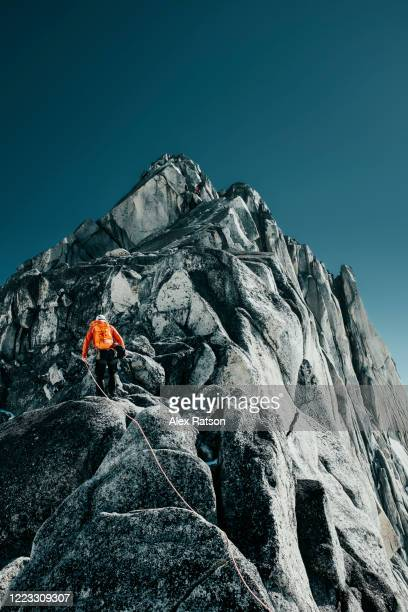 rock climber ascends west ridge of pigeon spire in bugaboo provincial park - mountaineering stock pictures, royalty-free photos & images