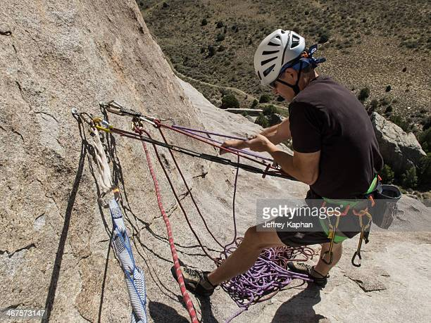 """Rock climber at the belay station on """"Big Time"""" a route on Castle Rock which is in Castle Rock State Park in southern Idaho. The climber is wearing a..."""