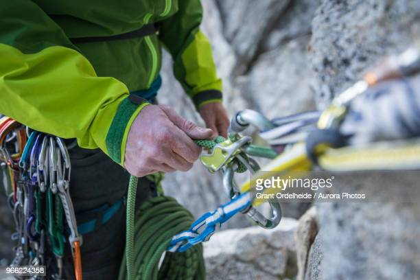rock climber belaying partner on lovers leap, lake tahoe, california, usa - messa in sicurezza foto e immagini stock