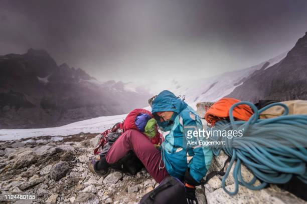 rock climber by climbing equipment shielding from extreme weather, el chaltén, south patagonia, argentina - cerro torre photos et images de collection