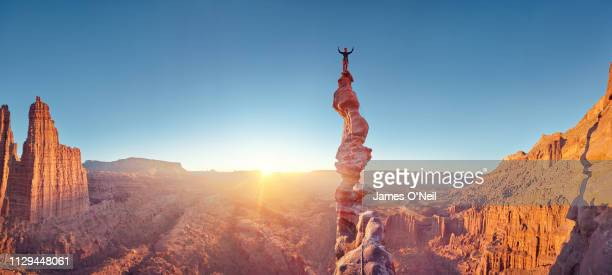 rock climber celebrating on top of summit of climb at sunset, ancient art, moab, usa - nature stock pictures, royalty-free photos & images