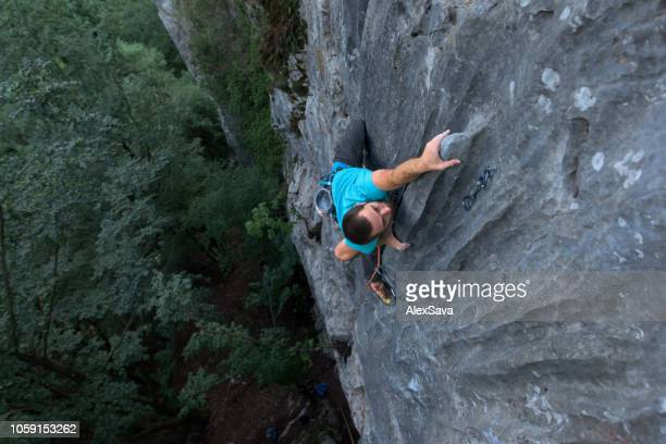 rock climber climbing on the rock wall - endurance stock photos and pictures