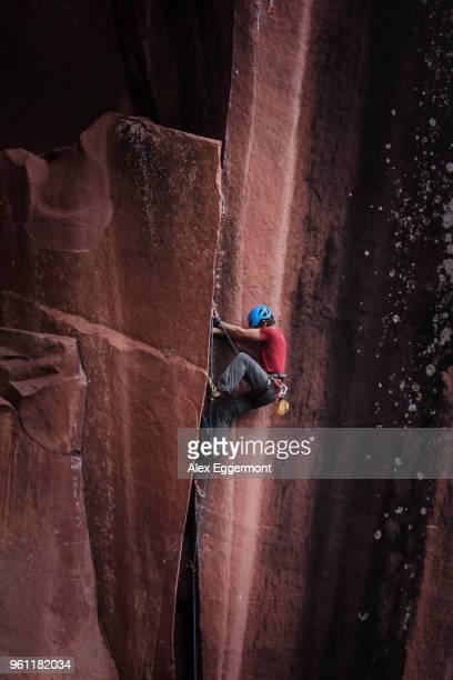 rock climber climbing sandstone rock, liming, yunnan province, china - yunnan stockfoto's en -beelden