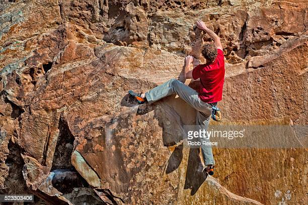 a rock climber climbing up a sandstone boulder - robb reece stock pictures, royalty-free photos & images
