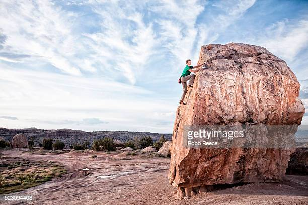 rock climber climbing up sandstone boulder, grand junction, mesa county, colorado, usa - robb reece stock pictures, royalty-free photos & images