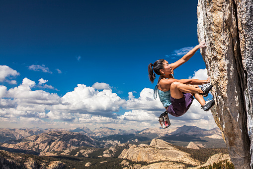 Rock climber clinging to a cliff. 527531592