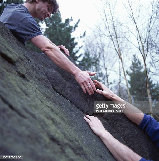 Rock climber extending hand to fellow climber