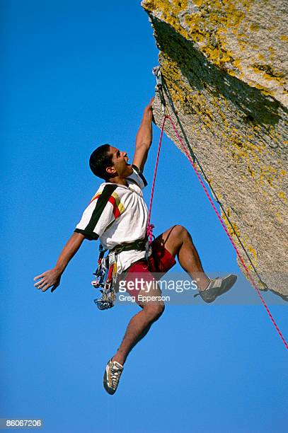 rock climber hanging from rock overhang - rock overhang stock photos and pictures