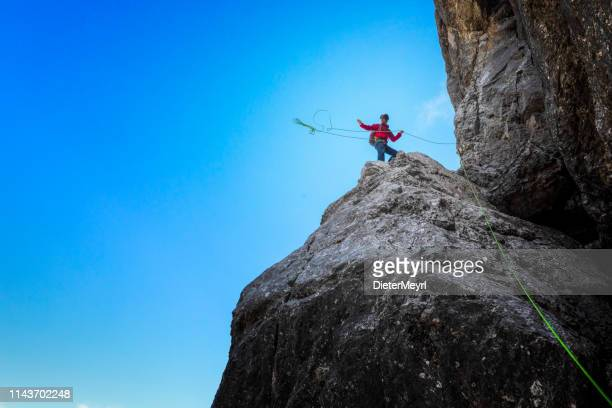 rock climber is throwing his rope from rock ledge - bavarian alps stock pictures, royalty-free photos & images