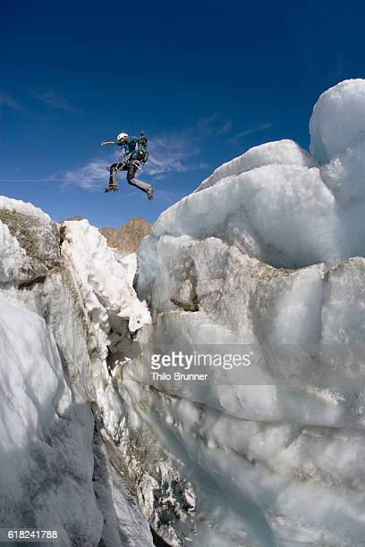 Rock climber jumping icy ridge