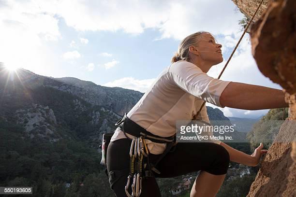 rock climber looks upwards to route above, sunrise - scalare foto e immagini stock