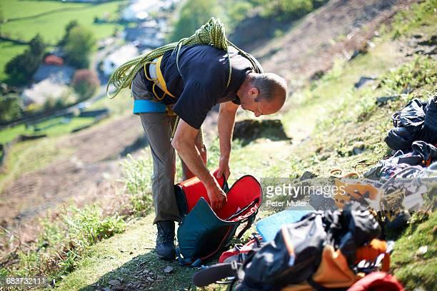 Rock climber on hillside preparing climbing equipment