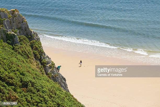 Rock climber overlooks a woman walking on a sandy beach on a hot summer's day. Tor Bay, Gower Peninsula, South Wales, UK.