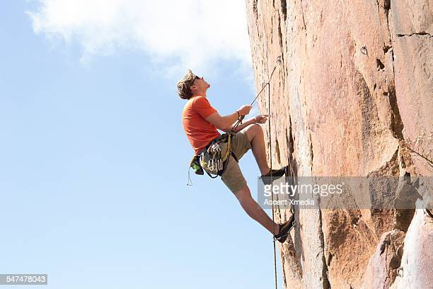 Rock climber pauses to view route ahead