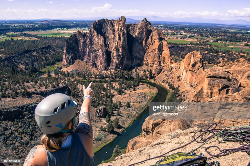 Rock climber pointing at rock formation, Smith Rock State Park, Terrebonne, Oregon, United States : Stock Photo
