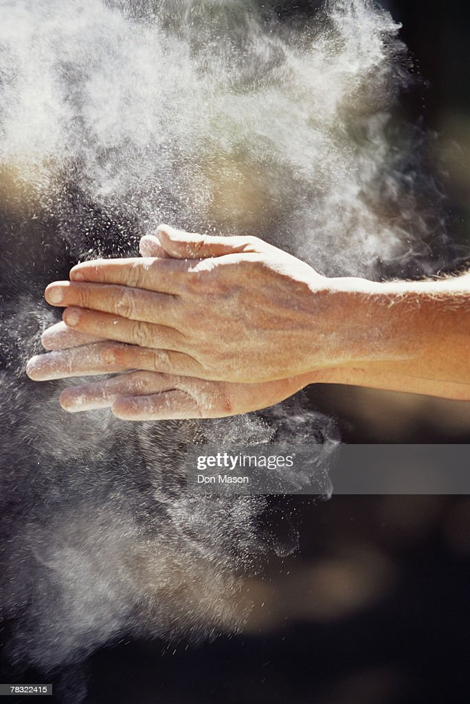 Rock Climber rubbing dust on hands : Stock Photo