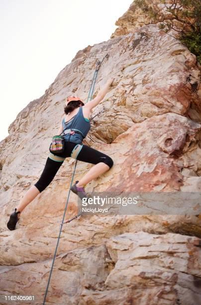 rock climber scaling a mountain - nicky pende foto e immagini stock
