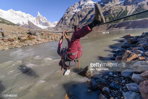 rock climber sliding on rope over river, el chaltén, south patagonia, argentina - cerro torre photos et images de collection