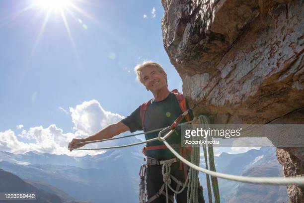 bergsklättrare ler när han drar klätterrepet genom karbinhake - pinnacle peak bildbanksfoton och bilder