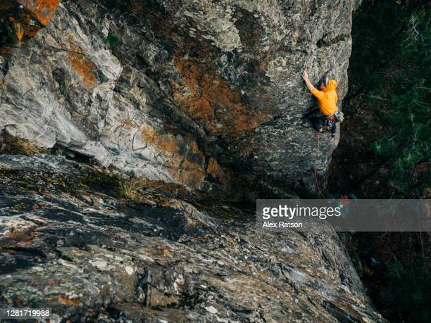 a rock climber stretches out his arm, reaching for a small hand hold on the side of a steep rock face - escaping stock pictures, royalty-free photos & images