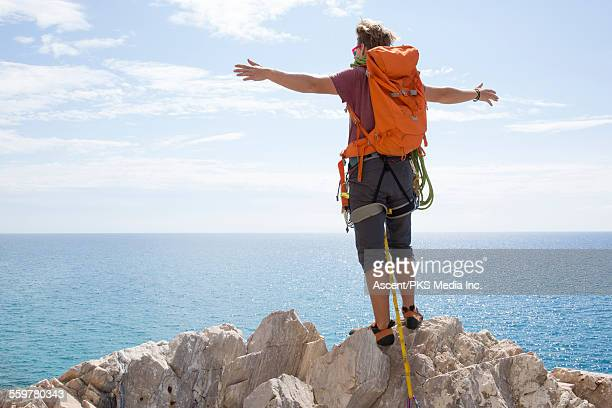 Rock climber stretcthes arms wide at top of climb