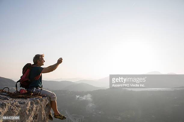 Rock climber takes pic with smart phone, summit