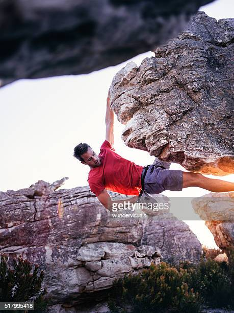 Rock climber with hand in chalk bag hanging on boulder