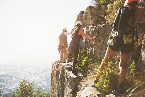 Rock climbers climbing rocks above sunny ocean - gettyimageskorea