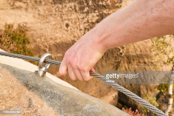 rock climber's hand hold on steel rope at steel bolt eye anchored in sandstone rock via ferrata. - sandstein stock-fotos und bilder