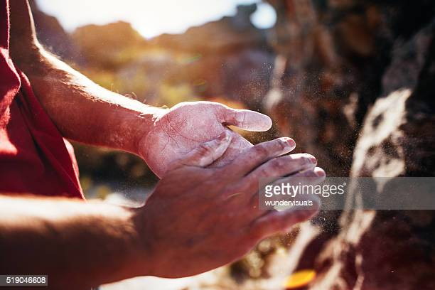 Rock climber's hands rubbing chalk in preparation for climbing ascent