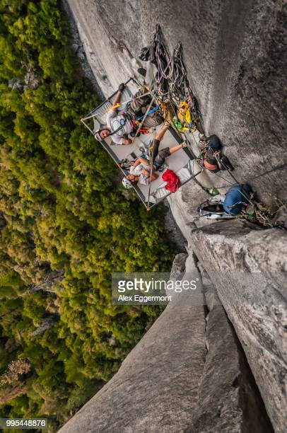 Rock climbers lying on portaledge, Muir Wall, on el Capitan, Yosemite Valley, California, United States
