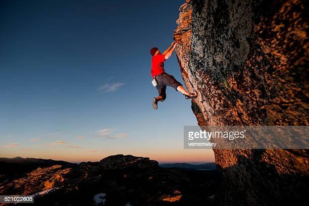Rock climbing up a steep cliff