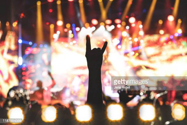 rock concert, concert lights, concert audience cheering, concert hands raised, rock hands, rock on - punk music stock pictures, royalty-free photos & images