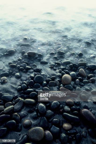 Rock Covered Beach with Calm Water