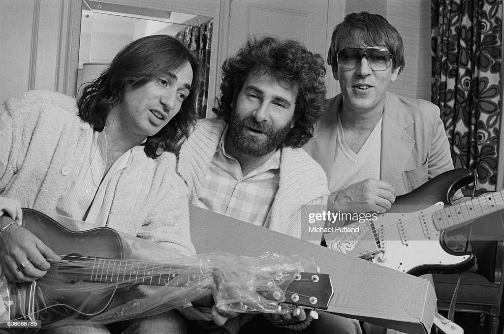 Rock duo Lol Creme (left) and Kevin Godley (centre) with English comedian Peter Cook (1937 - 19965), 1977. Cook is holding a guitar fitted with a prototype Gizmotron, (aka The Gizmo), an effects device invented by Godley and Cream, which uses serrated wheels to produce a bowing effect on guitar strings. Cook contributed to Godley and Creme's concept album 'Consequences', which was intended to showcase the Gizmotron. The device was later marketed commercially, but proved unsuccessful.
