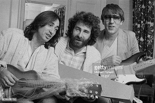 Rock duo Lol Creme and Kevin Godley with English comedian Peter Cook 1977 Cook is holding a guitar fitted with a prototype Gizmotron an effects...